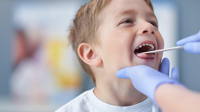 Mandelentzündung: Kleiner Junge streckt die Zunge leicht raus und lässt sich von einem Arzt den Rachen untersuchen.